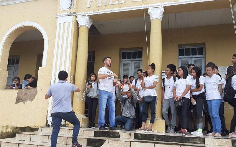 Tiago Oliveira ministrando aula de campo nas escadarias da prefeitura que tem estilo arquitetônico romano. Foto: Reprodução da internet